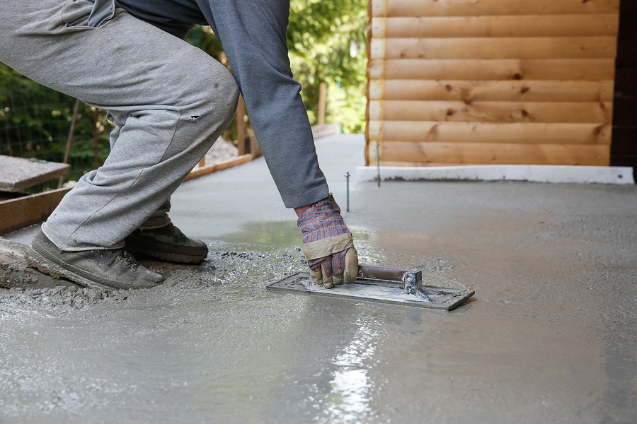 Mason leveling and screeding concrete floor base with square trowel in front of the house. Construction business, do-it-yourself, precision work around the house concept.